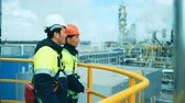 petrochemical plant : Two industrial workers discussion and pointing for inspection