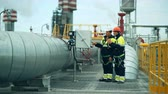 petrochemical : Engineers, in production plant as team discussing, industrial scene in background Stock Footage