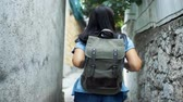 slovenya : Young woman with backpack on her shoulder walking along in old european town in summer day.