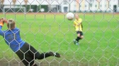 goleiro : A young boy scores a goal during a penalty shoot out. Shot in slow motion