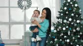 блаженный : Mother with her 10 months old baby girl decorating Christmas tree at living room
