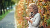 um jovem mulher só : Happy beautiful woman smile and using her phone in autumn park