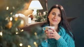 suéter : Young woman drinking coffee in front of the Christmas tree at home
