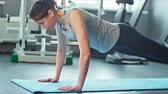 push ups : Young woman doing push-ups on exercise mat at gym. Female exercising on fitness mat at gym Stock Footage