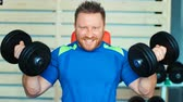 dumbell : Muscular man doing exercises with dumbbells at biceps in gym Stock Footage