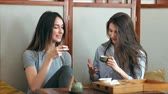 cosiness : Two pretty girlfriends talk and drink tea in cafe