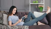 подключение : Young woman using digital tablet on sofa