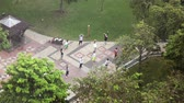 vista de cima : KUALA LUMPUR, MALAYSIA- OCTOBER 12, 2016 :The top view on group of the people doing sports exercises in KLCC Park and the central part of the city,Malaysia, Kuala Lumpur