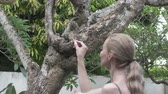 sıçan : The young woman feeds with nuts common treeshrew in a tropical garden