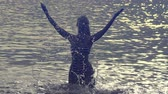 The silhouette of the young slender happy woman who stand in the sea and splashes water hands.slow motion