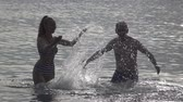 The silhouette of young people of the man and woman who stand in the sea and splashes water hands,slow motion