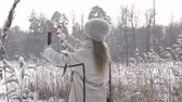 fotky : The young woman in a white jacket photographs a panorama of the coast of the winter forest lake on the smartphone,It is snowing