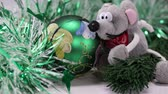 rat : The wind blows Christmas decorations in the form of a green painted ball, green rain and a soft toy in the form of a rat, side view from above, close-up Stock Footage