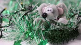 rat : Christmas garlands blink in the branches of an artificial spruce around a soft toy in the form of a rat, side view, close-up