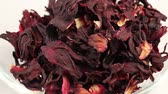 hibisco : Large leaves of Hibiscus tea fall in a transparent glass bowl, close-up Stock Footage