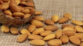 hearty : Almond nuts lie in a coconut shell and on a gray wicker napkin