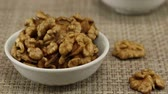 guloseima : Walnuts lie in a white bowl on a gray wicker background, close-up Stock Footage