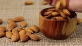 hearty : Male hand pours almonds into a brown wooden bowl, close-up