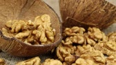 ramazan : Walnuts lie in half a coconut shell and on a gray wicker surface, close-up Stok Video