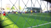 porazit : Mesh in football field with blurry soccer players playing and training soccer game. Soccer or football training in academy.