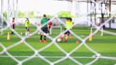 assistent : White mesh of goal with blurry soccer players are training to shoot ball to goal. soccer equipment in football academy. Stockvideo