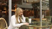ököl : businesswoman swears on the phone sitting in a cafe. It uses a Tablet PC