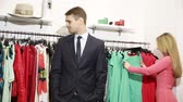 impatient : a man waits for his woman chooses a dress in a store. nervous and takes the first available clothes