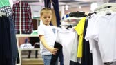 shopaholic : Cute smiling boy stands near clothes and choosing