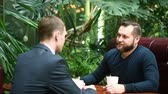 midlife : Two businessmen shaking hands in a cafe Stock Footage