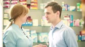 dispanser : Pharmacist woman offers the visitor a cure at the chemists shop