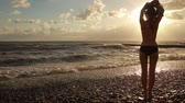 прибрежная полоса : girl undresses at the sea. silhouette of a beautiful woman.