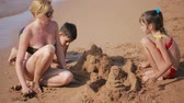 мама : Mother with children on the beach. build a sand castle. boy and girl Стоковые видеозаписи