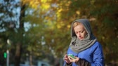 copy : Young smiling woman talking on cell phone in the autumn park.