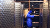 lined up : A woman chooses wine in a wine cellar.