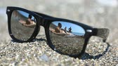 outstanding : Sunglasses on the sand, the beach with the resting people is reflected in the glasses.