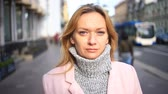 facing : A woman in a pink coat and sweater stands in the middle of a crowded street and looks at the camera Stock Footage