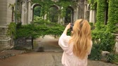 varanda : A tourists girl takes pictures of the beautiful collonade of an old castle twisted with ivy. Vídeos