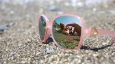 outstanding : Sunglasses on the sand, the beach with the resting people is reflected in the glasses. Pink glasses