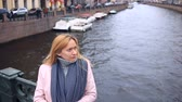 brilhando : Woman in pink coat and sweater stands on bridge over water background and looks at camera Stock Footage