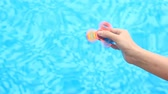 stres : A multicolored, red-yellow-blue hand spinner or spinner, rotating on the persons arm. A woman spinning a Fidget Spinner on a background of blue water in a pool