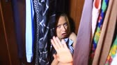 suddenness : The woman is hiding inside the wardrobe. They found her, she is frightened and screams. Copy space left