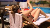 poesie : Young, elegant woman reading book on sunbed by pool