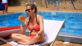 womens : Drunk pot-bellied woman in bikini and sunglasses drinking beer by the pool, Smokes a cigarette
