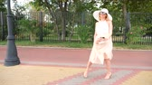 bolsa : An elegant woman in a hat and a white air dress strolls along the waterfront. General shooting. 4k, slow-motion