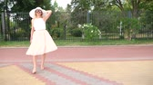 сцепление : An elegant woman in a hat and a white air dress strolls along the waterfront. General shooting. 4k, slow-motion