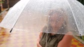 tükenme : A woman is standing under an umbrella. Summer torrential downpour. 4k, slow-motion