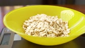 электроника : someone measures a piece of oatmeal, on an electronic scale in the kitchen. pour the rump into a deep round bowl, standing on a flat weighing platform. 4k, slow motion, dolly shot