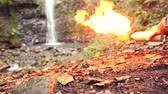 arremesso : 4k, slow motion. the tourist turns on the gas burner at the foot of the mountain, against the waterfall. Vídeos
