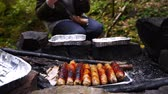 katarakt : 4k, slow motion. the tourist is cooking sausages on a mini grill in the forest. close-up