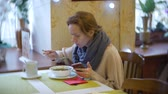 espinafre : a woman is having dinner in a cafe using a smartphone. 4k